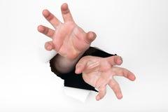 Hände, die durch Loch greifen Lizenzfreies Stockfoto