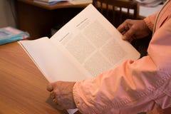 Hände, die ein Buch anhalten Lizenzfreie Stockfotografie