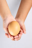Hände, die ein Ei anhalten Stockfoto