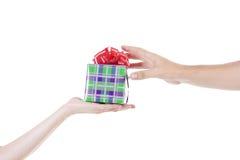 Hände, die ein Geschenk geben und empfangen Lizenzfreies Stockfoto