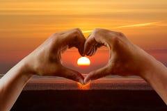Hände, die ein Herz mit aufgehende Sonne bilden Stockbild