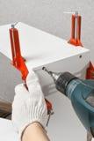 Hände, die ein Loch während des Zusammenbauens von Spanplattenmöbeln bohren stockfoto
