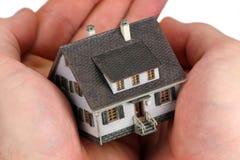 Hände, die ein Minihaus anhalten Stockbild
