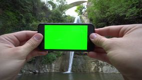 Hände, die ein Telefon mit einem grünen Schirm halten stock footage