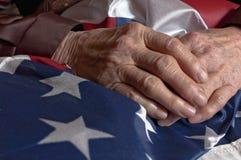 Hände, die eine amerikanische Flagge halten Lizenzfreies Stockfoto