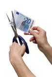 Hände, die eine Banknote mit Scheren kürzen Stockfotografie