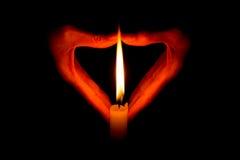 Hände, die eine brennende Kerze in der Dunkelheit halten Lizenzfreie Stockfotos