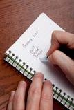 Hände, die eine Einkaufsliste schreiben Stockfoto