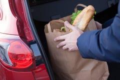 Hände, die eine Einkaufstasche im Autokofferraum laden stockfoto