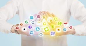 Hände, die eine Form mit beweglichen APP-Ikonen schaffen Lizenzfreie Stockfotos
