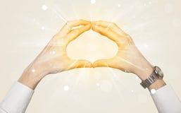 Hände, die eine Form mit gelbem Glanz schaffen Lizenzfreies Stockfoto