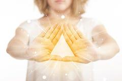 Hände, die eine Form mit gelbem Glanz schaffen Lizenzfreie Stockfotos