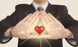 Hände, die eine Form mit glänzendem Herzen schaffen Lizenzfreie Stockfotos