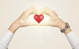 Hände, die eine Form mit glänzendem Herzen schaffen Lizenzfreies Stockfoto