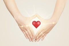 Hände, die eine Form mit glänzendem Herzen schaffen Lizenzfreie Stockfotografie