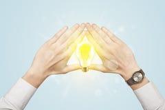 Hände, die eine Form mit Glühlampe schaffen Stockfotos
