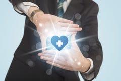 Hände, die eine Form mit Herzblaukreuz schaffen Lizenzfreie Stockfotos