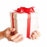 Hände, die eine Geschenkbox halten Mädchen, das kleine rote Geschenkbox mit dem Goldbogen lokalisiert auf weißem Hintergrund öffn Stockbilder