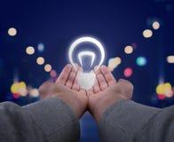 Hände, die eine Glühlampe halten Lizenzfreie Stockfotografie