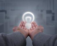 Hände, die eine Glühlampe halten Lizenzfreie Stockbilder