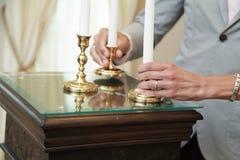 Hände, die eine Kerze anhalten Stockfotografie