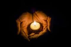 Hände, die eine Kerze halten Lizenzfreie Stockfotos