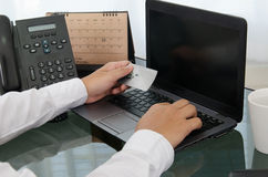 Hände, die eine Kreditkarte halten und Laptop verwenden Lizenzfreies Stockbild
