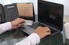 Hände, die eine Kreditkarte halten und Laptop verwenden Lizenzfreie Stockbilder