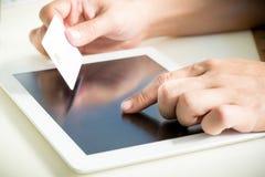 Hände, die eine Kreditkarte halten und Tabletten-PC verwenden Stockfoto
