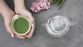 Hände, die eine Schüssel mit matcha Tee halten lizenzfreies stockfoto