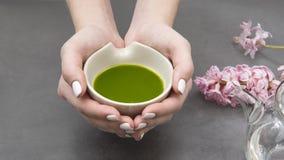 Hände, die eine Schüssel mit matcha Tee halten lizenzfreie stockbilder