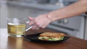 Hände, die eine Schale des heißen grünen Tees und des Sandwiches eine Tabelle entfernen stock footage