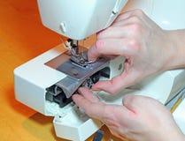 Hände, die eine Spule in einer Nähmaschine ersetzen Lizenzfreies Stockfoto