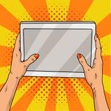 Hände, die eine Tablettenpop-art halten Weibliche Hände mit roter Maniküre halten eine Laptop-Computer Retro- Illustration der We Lizenzfreie Stockfotos