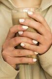 Hände, die einen abkühlenden Kaffee halten Lizenzfreie Stockbilder