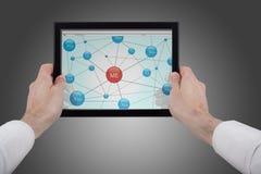 Hände, die einen Berührungsflächen-PC unter Verwendung der Sozialnetze anhalten Stockbild
