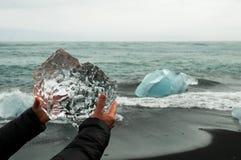 Hände, die einen Block des ursprünglichen Gletschereises halten stockfotografie