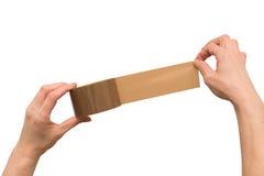 Hände, die einen braunen Klebstreifen halten lizenzfreie stockfotografie