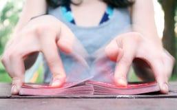 Hände, die einen Kartenstapel im Freien schlurfen stockfotos