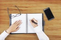 Hände, die einen Plan auf Tagesordnungsbuch machen Stockbild