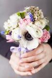 Hände, die einen schönen Frühlingsblumenstrauß halten Lizenzfreie Stockfotografie