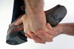 Hände, die einen Schuh aufladen Lizenzfreies Stockbild