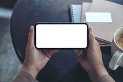 Hände, die einen schwarzen Handy mit leerem Bildschirm horizontal für das Aufpassen mit Kaffeetasse und Notizbüchern auf Tabelle  stockfotografie