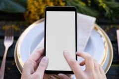 Hände, die einen Smartphone auf einem primaveral Hintergrund halten lizenzfreie stockfotos