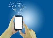 Hände, die einen Smartphone mit dem Fliegen von Glühlampen halten Lizenzfreie Stockfotografie