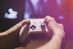 Hände, die einen Steuerknüppel und Videospiele in der Nacht f zu Hause spielen halten stockfotos