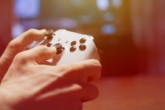 Hände, die einen Steuerknüppel und Videospiele in der Nacht f zu Hause spielen halten stockbild