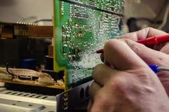 Hände, die elektrischen Stromkreis messen Stockfotografie