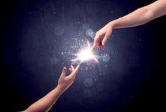 Hände, die erreichen, um einen Funken zu beleuchten Lizenzfreies Stockbild