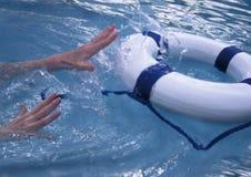 Hände, die für Schwimmweste erreichen Stockbilder